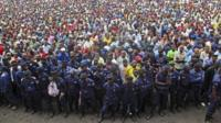 Congo government policemen, foreground, and civilians gather during a M23 rally in Goma, Congo