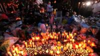 Candles are lit at a memorial for the shooting victims
