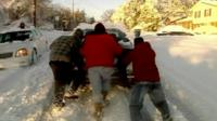 Three people pushing a car stuck in the snow
