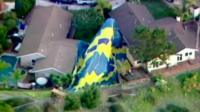 the balloon draped over a tree and a house