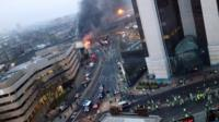 Smoke pours from the burning debris of a helicopter which crashed in London