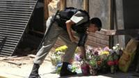 Policeman laying flowers outside club in Brazil