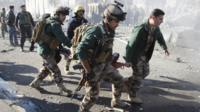 A wounded person is carried by soldiers at the site of a suicide bomb attack in Kirkuk