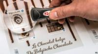 A Bpost worker uses a magnifier to check the quality of newly printed chocolate stamps at the Bpost