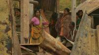 Bangladesh villagers stand in damaged buildings after attack