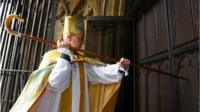 The Most Reverend Justin Welby, strikes three times on the West Door of Canterbury Cathedral