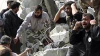 People search for casualties under the rubble at a site hit by what activists say was an air strike in Daiaat Al-Ansari neighborhood, Aleppo March 30, 2013.