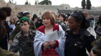 "Israeli policewomen detain a member of the religious group ""Women of the Wall"""