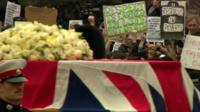 Protesters behind Margaret Thatcher's coffin