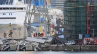 Rescuers search what is left of the control tower of the port of Genoa