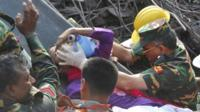 Rescuers carry a survivor pulled out from the rubble of a building that collapsed in Saver
