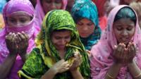 Bangladeshi family members of missing garment workers offer prayers in front of the rubble of a nine-storey building collapse in Savar