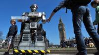"""People look at a mock """"killer robot"""" in central London - part of a protest calling for a ban on such weapons in London on 23 April 2013"""
