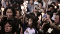 A child (C) takes part in a candlelight vigil held to mark the 24th anniversary of the 1989 crackdown at Tiananmen Square, in Hong Kong, on June 4, 2013