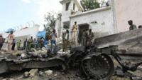 """Security agents stand near the scene of a suicide bomb attack outside the United Nations compound in Somalia""""s capital Mogadishu"""