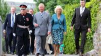Prince Charles and the Duchess of Cornwall walk to the Boathouse in Laugharne