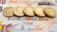 Pound coins on a bank note