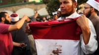 A man holds up a bloodied shirt at a pro-Morsi rally in Cairo. Photo: 8 July 2013