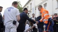 French President Francois Hollande (C) shakes hands with a rescue worker