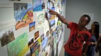 Ethiopian refugee points at art