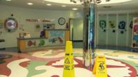 Ward reception with wet floor notices