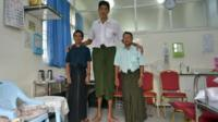 Win Zaw Oo standing next to two men of average height