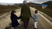 A female refugee holds her children's hands