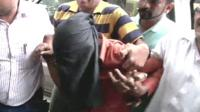 A fifth suspect is restrained by officials