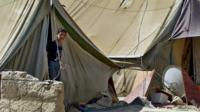 A Syrian refugee boy looks outside his tent, at a temporary refugee camp in the eastern Lebanese town of Marj
