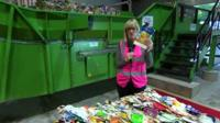 Steph McGovern holds carton at recycling plant