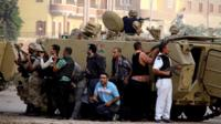 Egyptian security forces take cover during clashes with suspected militants (not pictured) in the town of Kerdasa,
