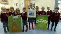 Children pose with paintings