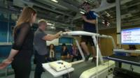 Man on a treadmill being monitored by health professionals
