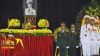 Soldiers stand to attention next to coffin