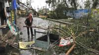 An man salvages a table stuck in uprooted trees which fell during Cyclone Phailin in Berhampur, India