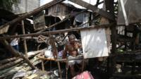 A Filipino resident sits inside his damaged house after Typhoon Nari hit San Miguel town