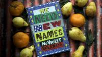 Book of We Need New Names, surrounded by fruit