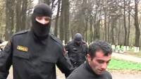 Masked special forces holding suspect