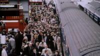 Passengers get off a train onto a crowded platform
