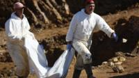 Two men carrying a bag of human remains