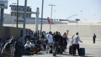 Evacuated passengers wait on a road after a shooting at the airport