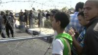 Barbed wire separates the protesters from the security forces
