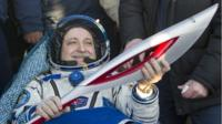 Russian cosmonaut Fyodor Yurchikhin holds the torch of the 2014 Sochi Winter Olympic Games after Soyuz TMA-09M capsule landed in a remote area in central Kazakhstan Monday, Nov. 11, 2013