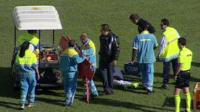 Officials help an injured player