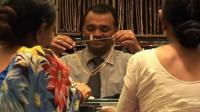 Women look at salesman's gold necklace