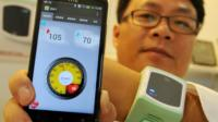 A staff displays TCB International Corp.'s new products, the 'Health Bracelet' and its APP 'Blood Management Your (BMY)