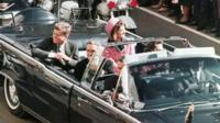 JFK and wife Jackie drive through Dallas in the motorcade
