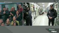 A split-screen shot from RTVV's last broadcast showing workers on one side in a TV studio and police officers waiting to pull the power plug on the other side