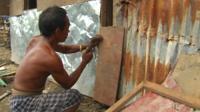 Man rebuilding hut