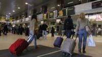 Romanians carry their luggage at Otopeni airport near Bucharest